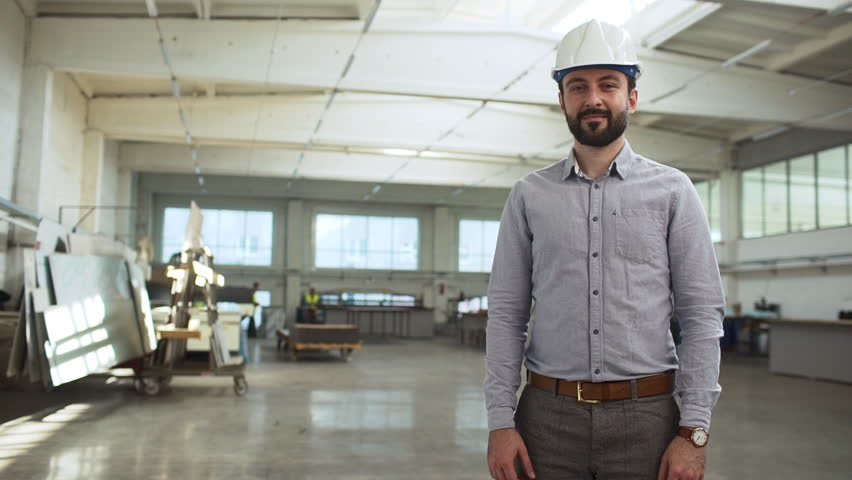 Portrait of adult bearded man, executive manager or engineer, wearing suit and helmet monitoring process of work in factory room slow motion