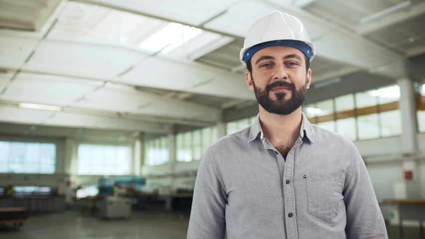 Portrait of adult european man wearing shirt and helmet standing in big manufacture room with professional equipment, for industrial production slow motion