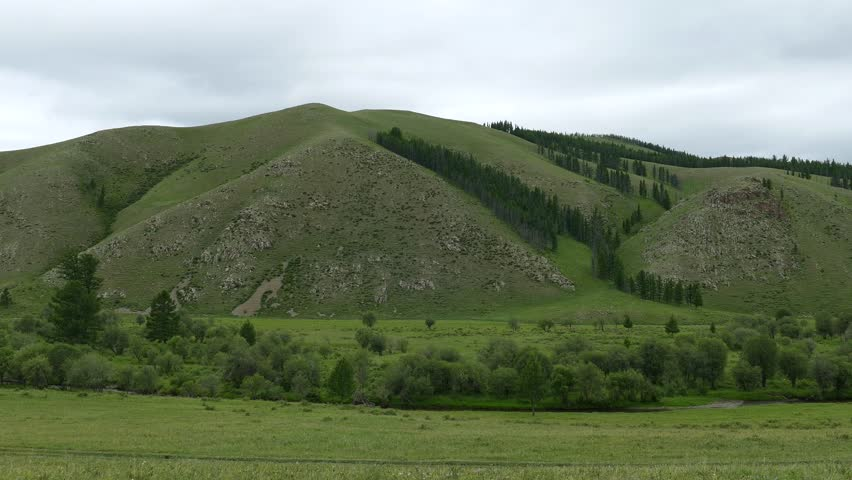 Low wooded mountains and a little river under the cloudy sky. The Mongolian Savannah. A summer cloudy day.
