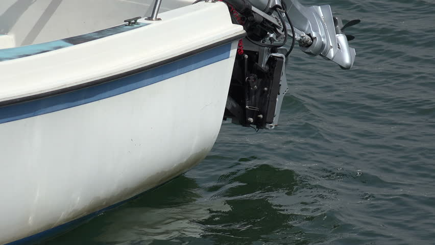 Closeup of a boat with an outboard motor in the harbor