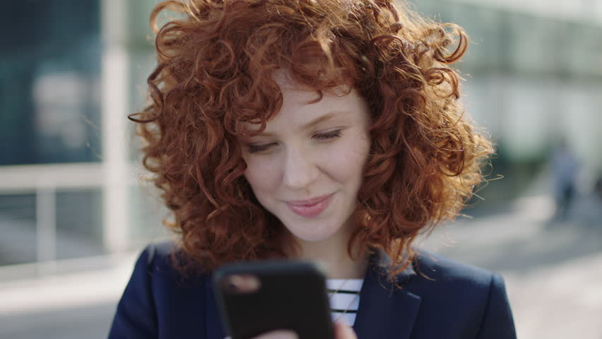 beautiful young business woman laughing texting on phone portrait of redhead college student corporate executive #1011757970
