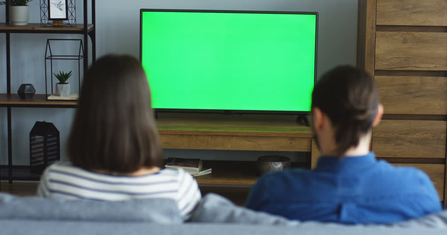 Back view on the young couple sitting in the living room and watching TV with green screen, men changing channels with a remote control. Chroma key. Indoors