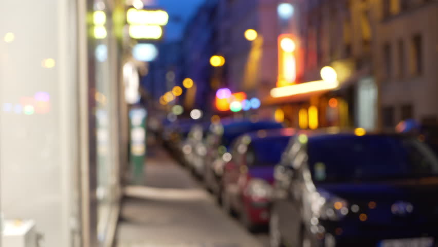 Out of focus background plate of cars parallel parked on city street next to shops in Europe. Attractive night scene with window shopping access