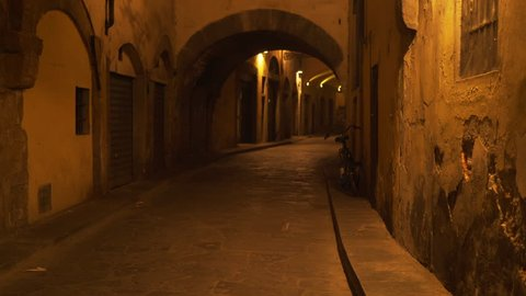 Background plate of low lighting small street alley in Europe. Blurred background plate of archway on an empty European street