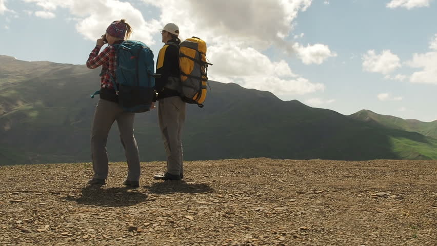 Hiking in Caucasus mountains. Woman Man Travelers with Backpacks Hiking In Mountains. Mountaineering sport lifestyle concept. Couple of hikers on a mountain. Young people on mountain hike summer.    Shutterstock HD Video #1011793580