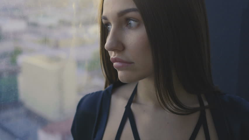 Sensual girl is standing next to the window   Shutterstock HD Video #1011807290