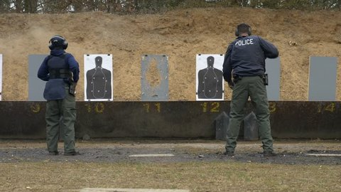 A team of police officers shoot their weapons at a gun range for target practice.