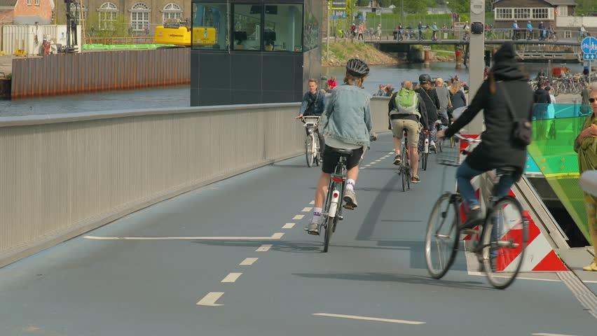 COPENHAGEN, DENMARK - MAY 09, 2018: People riding bikes on Inderhavnsbroen, cyclist and pedestrian bridge opened in 2016 in the harbor of Copenhagen