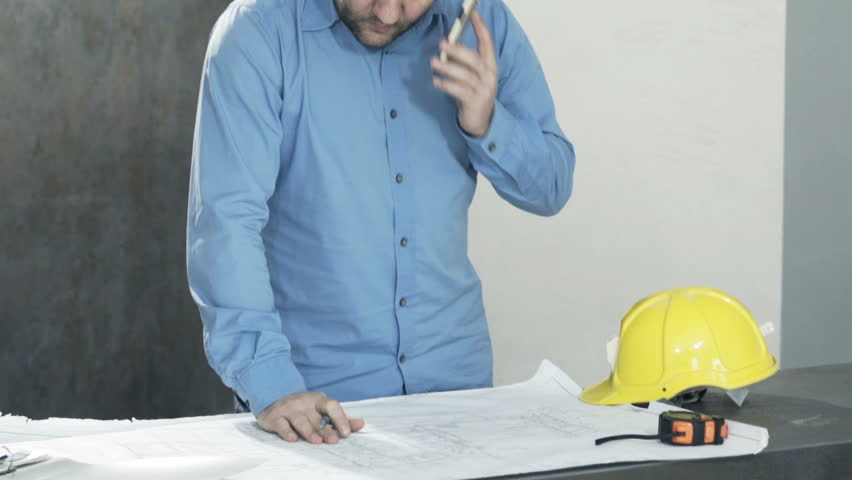 Angry man with blueprints talking on cellphone and checking wall at new home  | Shutterstock HD Video #1011876320