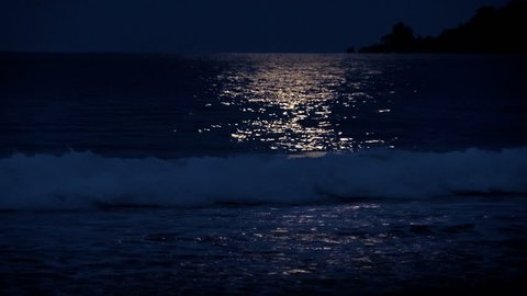 Full moon reflection on a Caribbean Beach. White wake on the waves of the sea in the tropics. Waves breaking on the shore in the light of the moon.