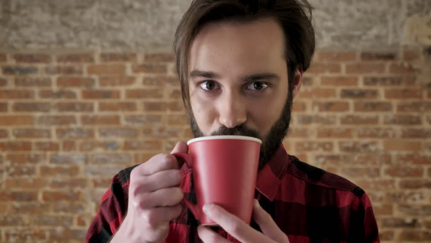 Yound attractive man with beard is drinking tea, watching at camera, brick background | Shutterstock HD Video #1011898940