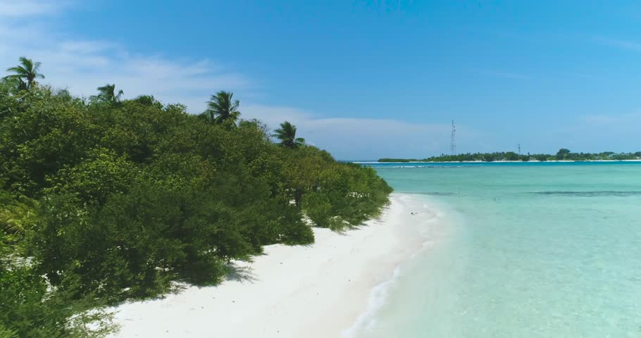Scenic Aerial Drone Fly Over Shot Above Maldives Tropical Island, Palm trees, Heaven and calm scene. Lifestyle