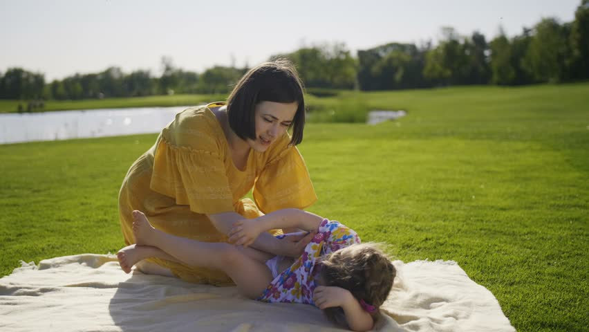 Funny mother and daughter having fun on green grass lawn. Young mom blowing into little girl's stomach tickling her. Toddler down syndrome daughter enjoying and laughing together with mother on meadow