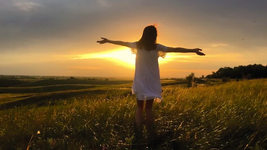 Beautiful girl wearing white dress running through beautiful field at sunset. Young woman jogging at the meadow and enjoying freedom. Summer leisure at nature concept. | Shutterstock HD Video #1011914060