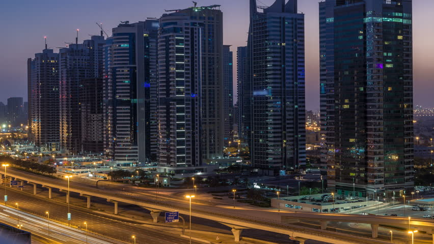 Aerial view of Jumeirah lakes towers with illuminated skyscrapers night to day transition timelapse with traffic on sheikh zayed road and metro line. Rooftop view from Dubai marina before sunrise