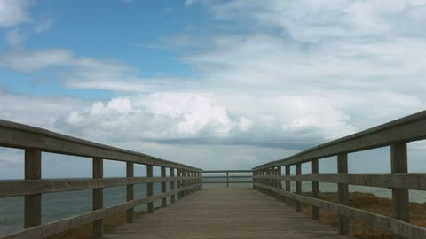 Horizon sky and sea slow timelapse over pier on the cliff