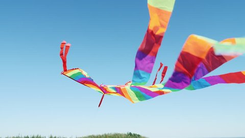Rear view of a kite flying high in a blue sky close up. Bird's eye view