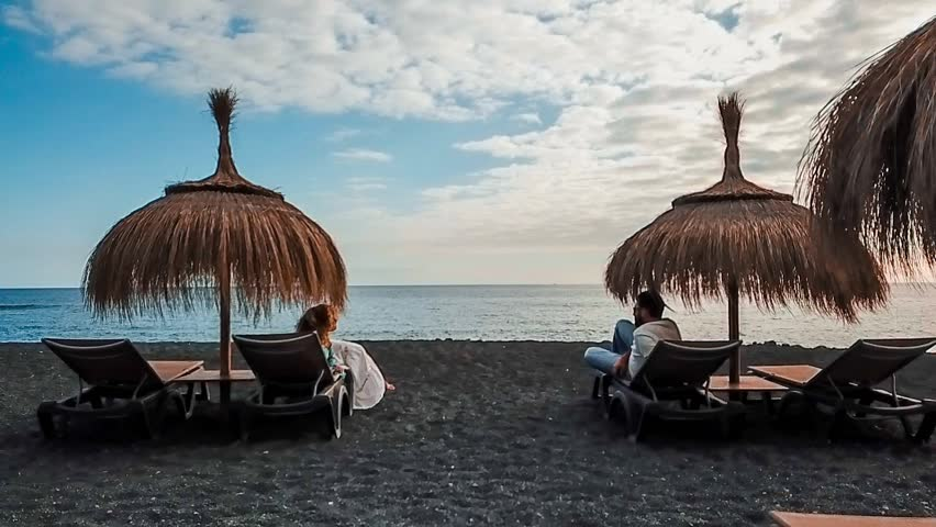 Nice couple in love seats and lay down at the beach on the seats under the umbrellas to protect from the sun. tenerife summer vacation time leisure to anjoy the season and the sunset that come