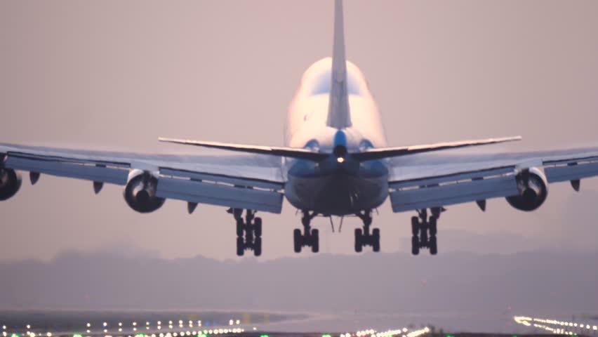 4K Passenger airplane landing during sunrise