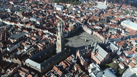 Aerial of Belfry of Bruges in Dutch Belfort van Brugge is a medieval bell tower in the centre of Bruges Belgium and one of the citys most prominent symbols also showing market square in background 4k