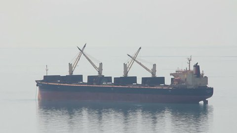 Cargo ship on calm sea surface in faint morning light in foggy air
