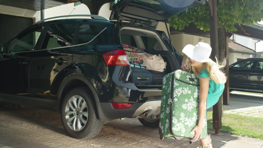 SLOW MOTION, LENS FLARE: Excited young woman struggles to close the trunk of her black SUV after packing too much luggage for her trip. Funny shot of girl trying to close the back of her big car.