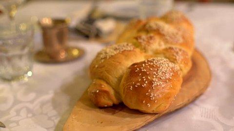 Friday evening Jewish Shabbat dinner table, holy Challah bread, close up