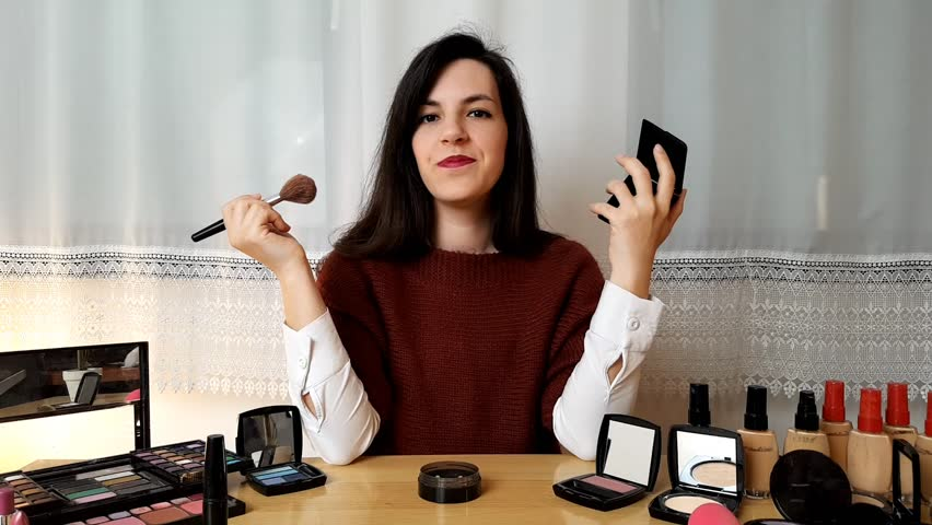 Woman doing make up vlog tutorial. Young brunette female doing video blog about bronzer application, at home.