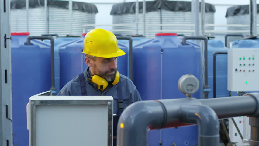 Medium shot of middle aged man with yellow hard hat and earmuffs operating fertigation machine when working in industrial greenhouse complex