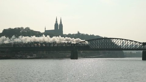 Prague, Czech Republic. Old Retro Locomotive Moving In Bridge. Basilica Of St. Peter And St. Paul On Background