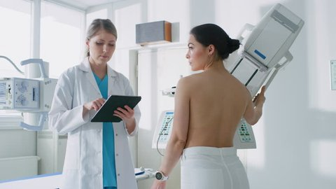 In the Hospital, Mammography Technologist / Doctor adjusts Mammogram Machine for a Female Patient. Friendly Doctor Explains Importance of Breast Cancer Prevention Screening. Shot on RED EPIC-W 8K.
