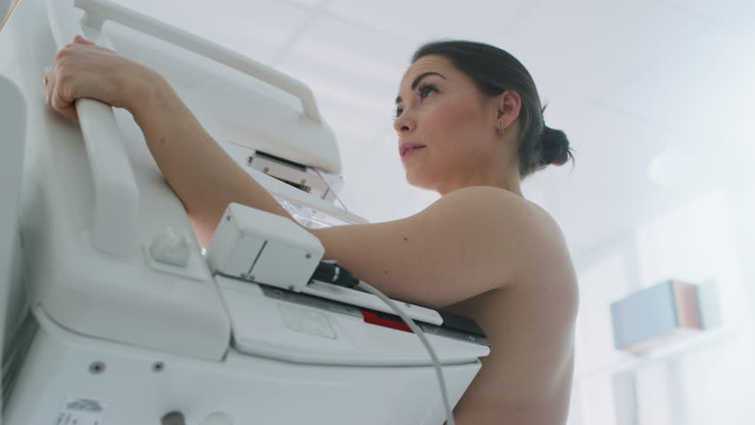 In the Hospital, Low Angle Portrait Shot of Topless Female Patient Undergoing Mammogram Screening Procedure. Healthy Young Female Does Cancer Preventive Mammography Scan.  Shot on RED EPIC-W 8K Camera