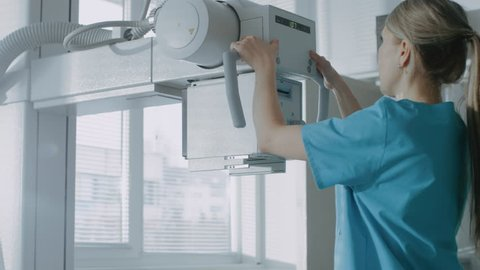 In the Hospital, Female Technician adjusts X-Ray Scanner / Machine. Modern Hospital with Technologically Advanced Medical Equipment and Professional Personnel. Shot on RED EPIC-W 8K Camera.
