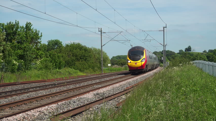 Northamptonshire,UK - June 7, 2018: A Virgin Trains Pendolino tilting electric express passenger train traveling north at speed on the West Coast mainline in Northamptonshire England. | Shutterstock HD Video #1012075520