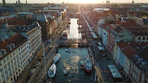 Amzing Backlight sunset footage from Copenhagen, Denmark. bridge in Nyhavn New Harbour canal and entertainment district. Aerial Video footage view from the top. forward movement. Sunset golden light