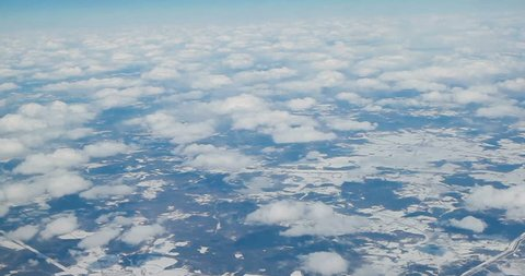Stunning footage of aerial view above clouds from airplane window with blue sky. view from the airplane window to the blue sky and white clouds. view of the earth from the sky through the clouds