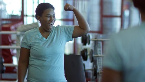 Medium shot of charismatic black woman having fun in gym: she looking in mirror and flexing muscles while laughing and making faces