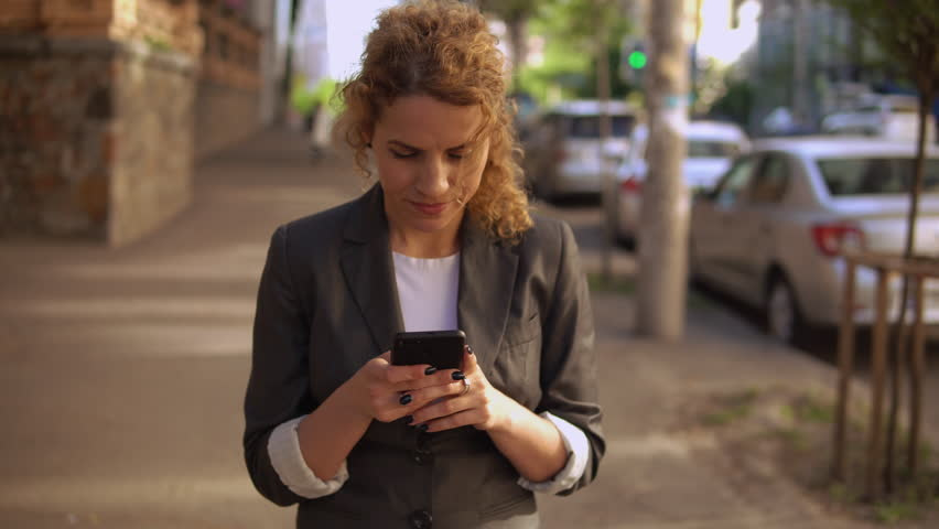 Beautiful woman walking down the street texting message on smartphone. spring season in city | Shutterstock HD Video #1012090460