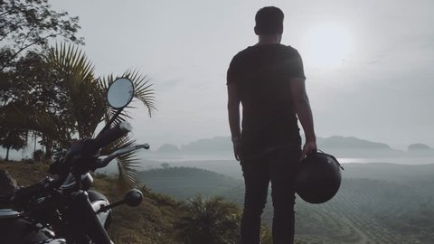 Back view of cool traveler standing in front of his chopper motorbike and admiring beautiful tropical mountain view during cloudy early morning - video in slow motion