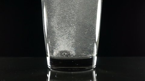 Effervescent vitamin C tablet bubbles in glass of water. Pill in slow motion close up.