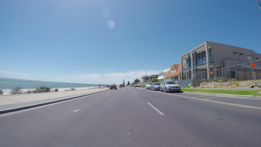 Vehicle POV, driving along The Esplanade, Henley Beach, South Australia, with views of ocean and beach, and homes overlooking the sea.