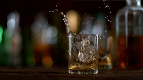 Ice dropped into glass of whisky in super slow motion. Shot with high speed cinema camera, 1000fps.