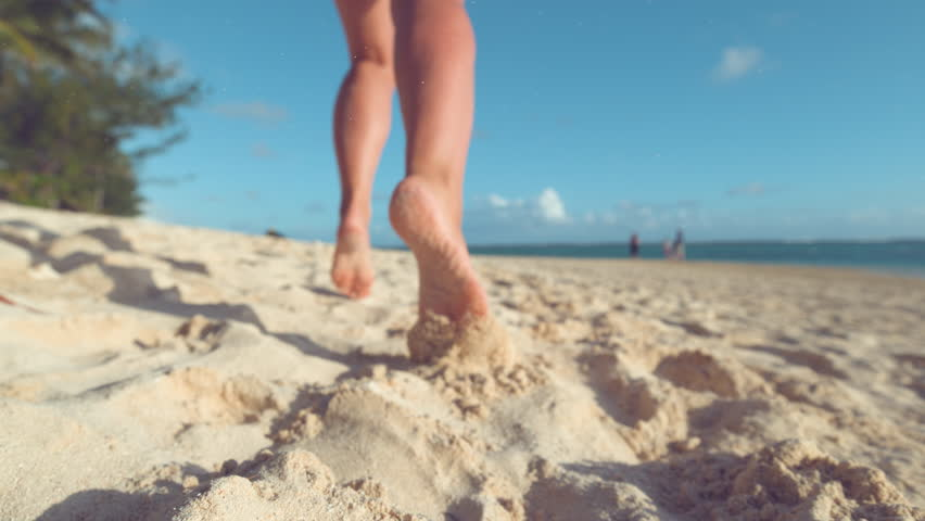 SLOW MOTION, CLOSE UP, LOW ANGLE, DOF: Particles of sand fly in the air as unrecognizable woman jogs barefoot on the tropical beach on remote island. Cheerful girl runs along ocean in the summer sun. | Shutterstock HD Video #1012187810
