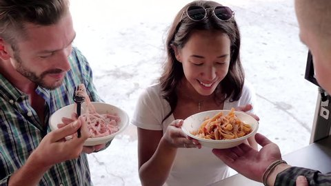 Young couple customers enjoying pasta that just ordered at counter of food truck