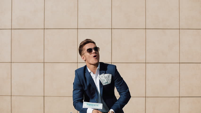 Young happy businessman scatter the dollars and funny dancing in the street. He walking near the office center, slow motion. Money rain, successful business
