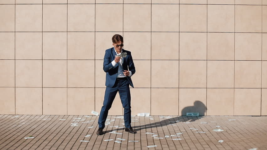 Young happy businessman scatter the dollars and dancing in the street. It is located near the office center, slow motion. Successful business | Shutterstock HD Video #1012211990