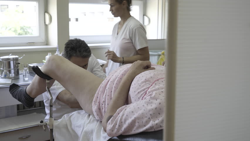 Male gynecologist performs gynecological examination of woman, nurse assisting doctor and adjusts light on lamp, female patient lying on medical review in ambulance room at gynecology ward, healthcare