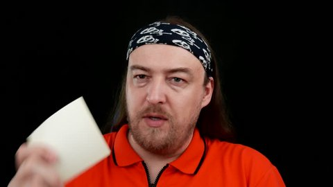 Adult man with long hair and a beard and a scarf with skulls, in an orange T-shirt. Shakes his head disapprovingly and postpones note paper.