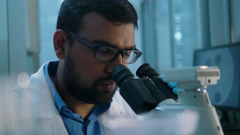 Life scientist working at a laboratory. Young indian male life scientist looking at samples through microscope.