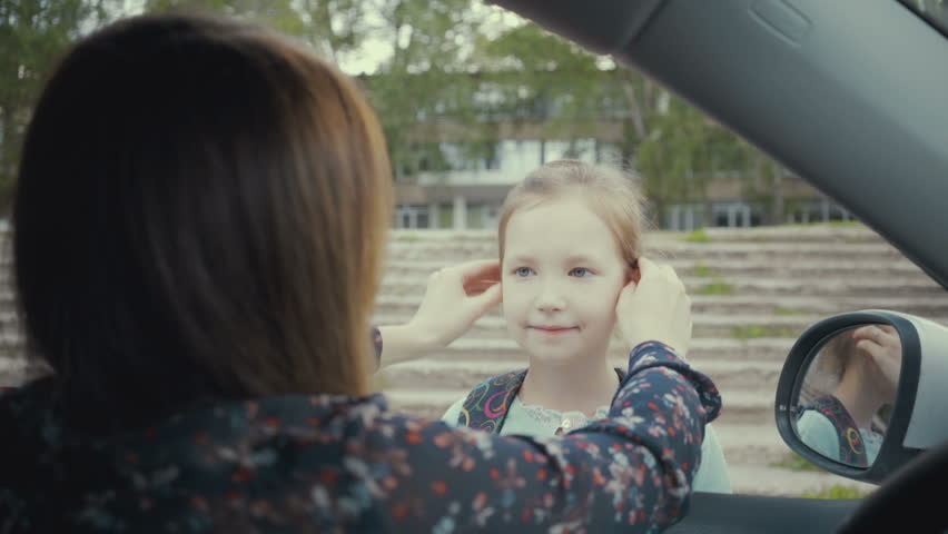 Mom sits in the car and escorts her daughter to school | Shutterstock HD Video #1012241150